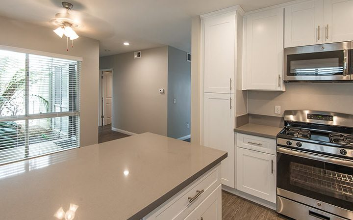Sunny kitchen interior with range and built-in microwave at The Retreat at Thousand Oaks apartments
