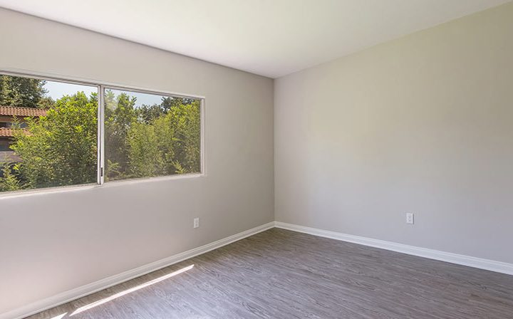 Spacious bedroom interior at The Retreat at Thousand Oaks apartments with sunny view of trees