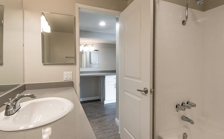 The Retreat at Thousand Oaks apartment bathroom interior with side mirror and bathtub shower combo
