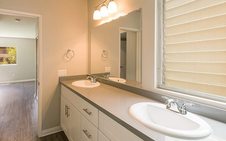 Bathroom interior with sunny hallway and two sinks at The Retreat at Thousand Oaks apartments