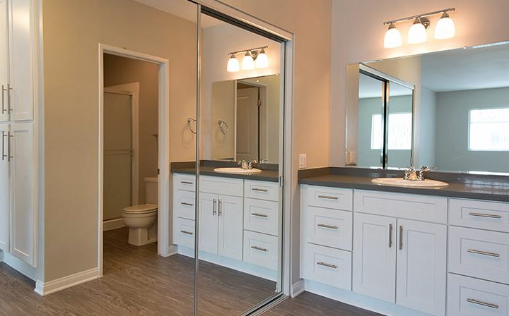 Well lit bathroom interior with mirrored closet doors at The Retreat at Thousand Oaks apartments