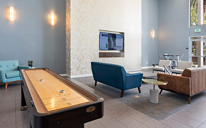 Shuffleboard and television sitting area in The Retreat at Thousand Oaks apartments clubhouse