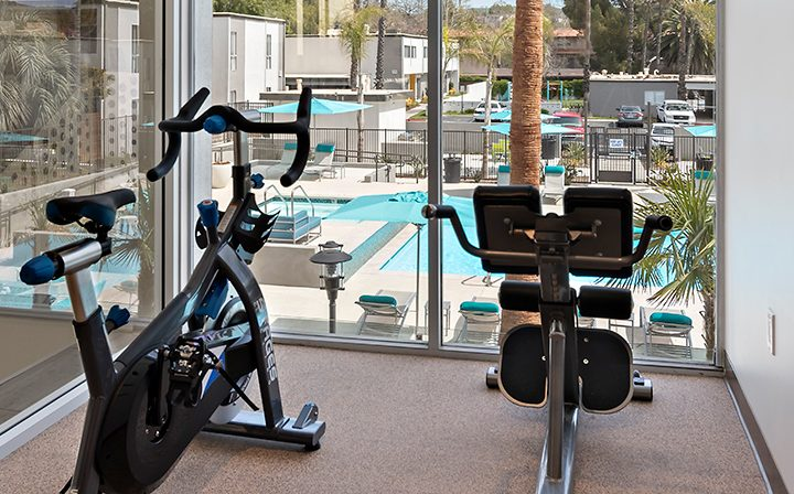 Bicycle workout machines at The Retreat at Thousand Oaks apartments fitness center with pool view