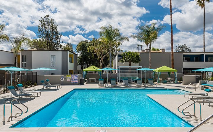 Pool view at The Retreat at Thousand Oaks apartments with palm trees and blue and green umbrellas