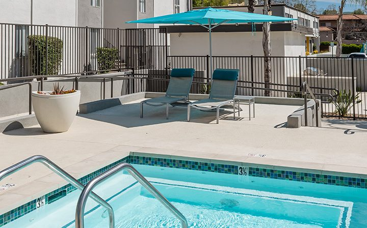 Hot tub spa and umbrella-shaded sitting area with chairs at The Retreat at Thousand Oaks apartments