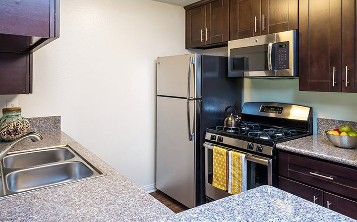 Furnished kitchen with brown cabinets at The Ruby Hollywood, Los Angeles apartments in Hollywood