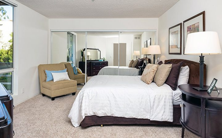 Furnished bedroom with mirrored closet at The Ruby Hollywood, Los Angeles apartments in Hollywood