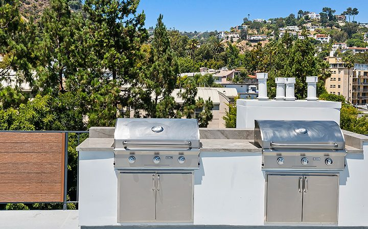 BBQ grills on rooftop overlooking city at The Ruby Hollywood, Los Angeles apartments in Hollywood