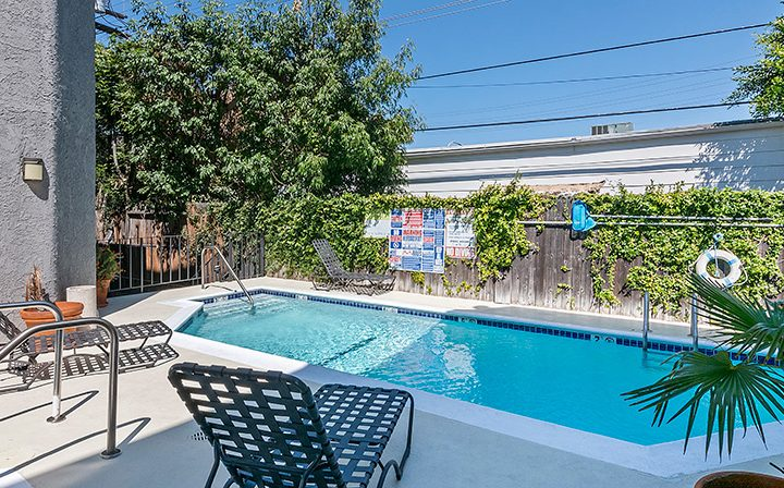 Pool by wood fence and chairs at Villa Bianca, West Hollywood apartments in Los Angeles