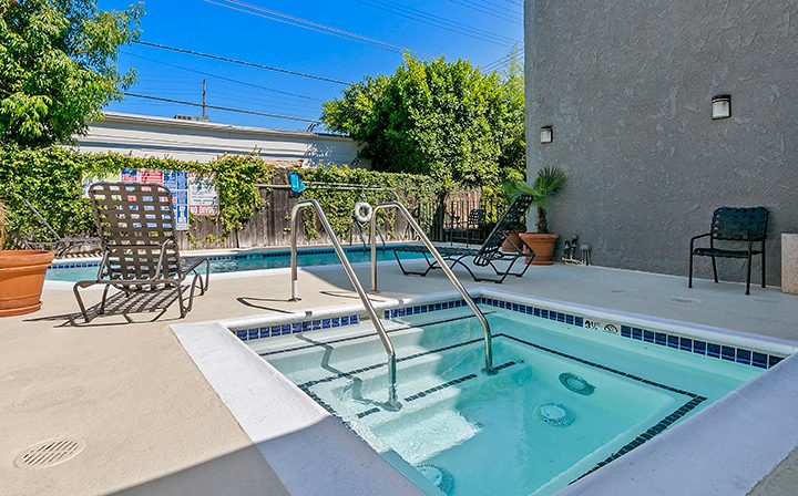 Square hot tub by pool and seating at Villa Bianca, West Hollywood apartments in Los Angeles