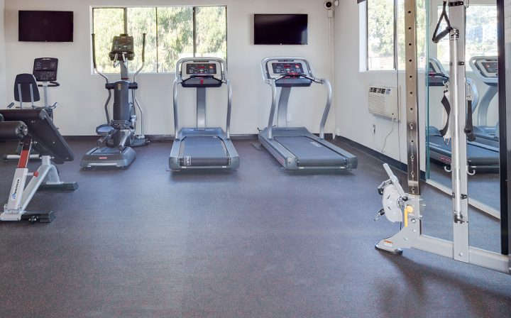 Machines and TVs in fitness center at Villa Esther, West Hollywood apartments in Los Angeles