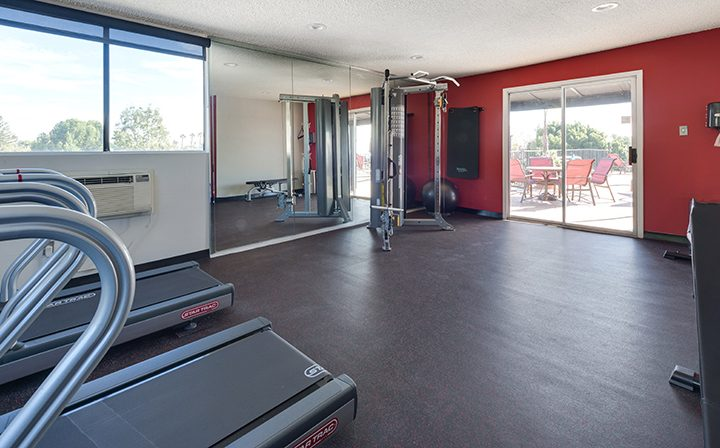 Fitness center with red wall and machines at Villa Esther, Los Angeles apartments in West Hollywood