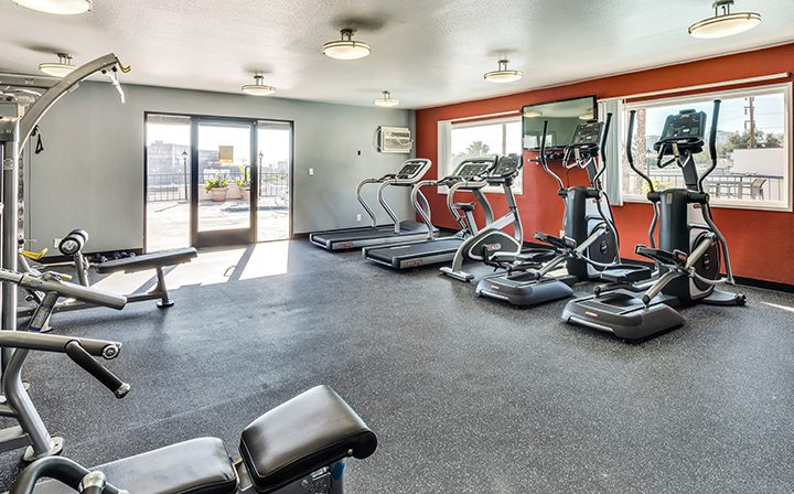 Fitness center with orange wall at Villa Francisca, Los Angeles apartments in West Hollywood