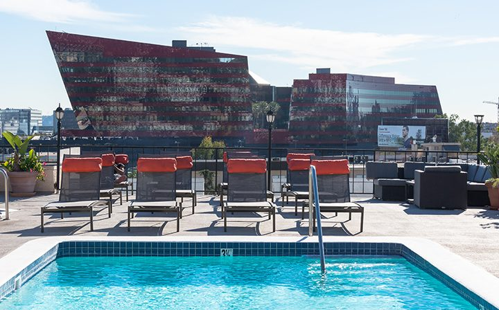 Orange-padded chairs by rooftop pool at Villa Francisca, Los Angeles apartments in West Hollywood
