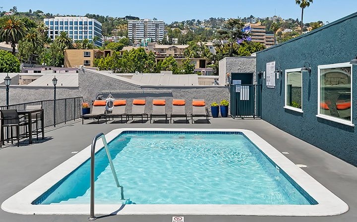Rooftop pool with orange-padded chairs at Villa Francisca, West Hollywood apartments in Los Angeles