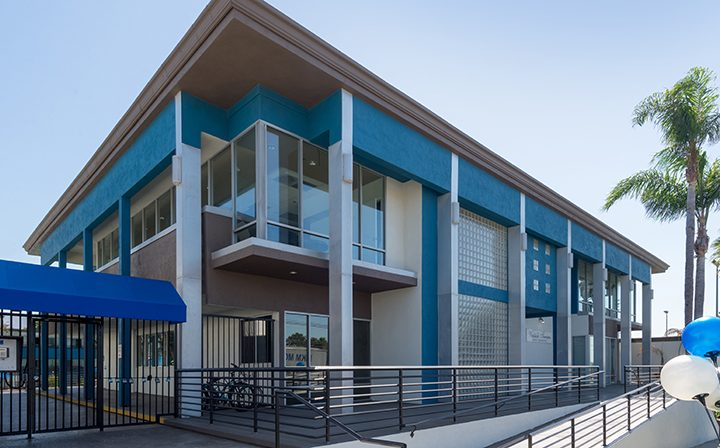 Two-story clubhouse with blue accents near pool at Westside Terrace, apartments in West Los Angeles
