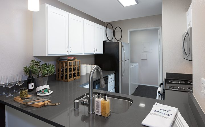 Furnished kitchen with white cabinets and black counter at Willow Creek, San Jose apartments
