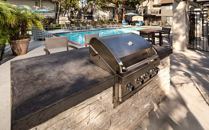 BBQ grill in front of pool and potted plants at Willow Creek, apartments in San Jose