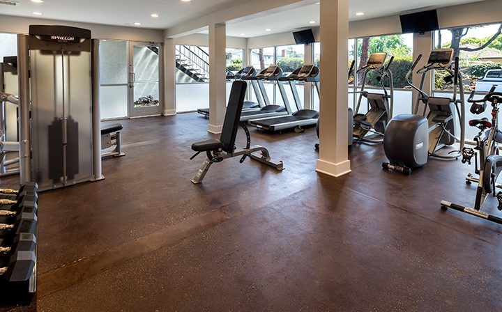 State-of-the-art fitness center with machines and brown floor at Willow Creek, San Jose apartments