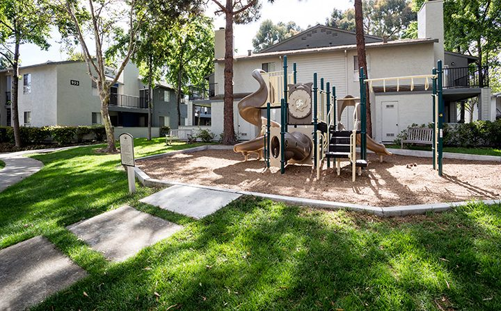 Grassy path leading to children's playground with spiral slide at Willow Creek, San Jose apartments