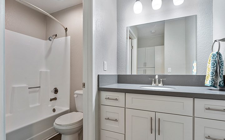 Bathroom with white cabinets, vanity, and shower/tub combo at Willow Creek, San Jose apartments