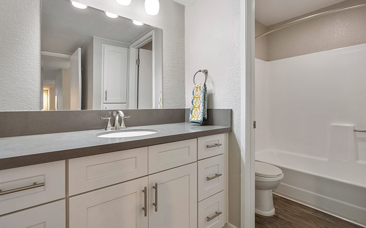White bathroom with vanity and shower/bathtub combo at Willow Creek, apartments in San Jose