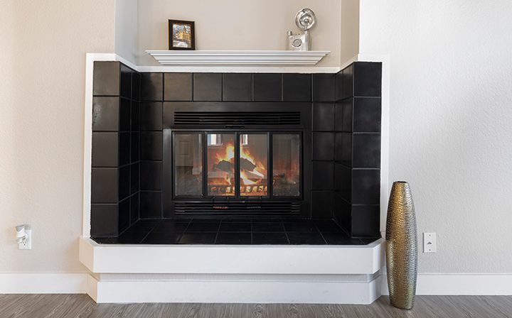 Fireplace with black tile in unfurnished living room at Willow Creek, San Jose apartments
