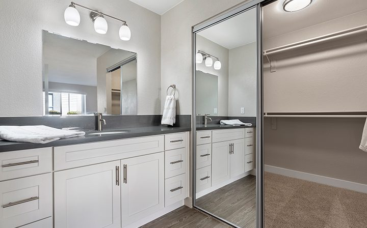 Mirrored closet next to bathroom with vanity and lights at Willow Creek, San Jose apartments