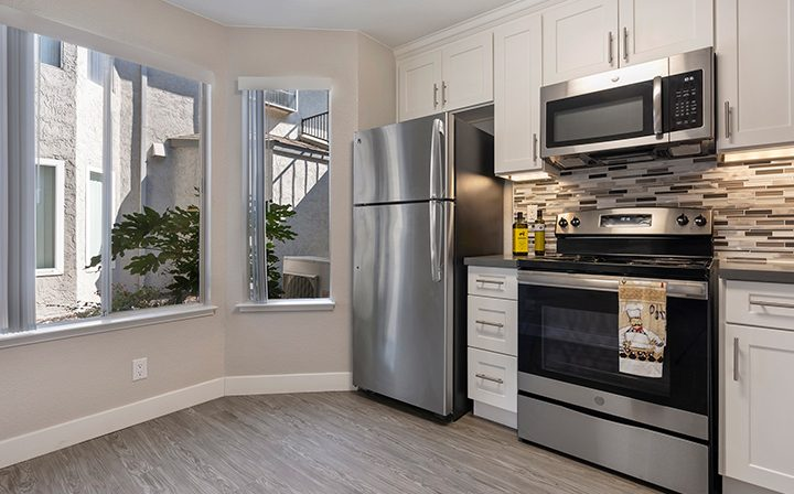 Kitchen with bay window and white cabinets at Willow Creek, apartments in San Jose