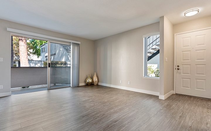 Large, unfurnished living room with balcony exit at Willow Creek, San Jose apartments