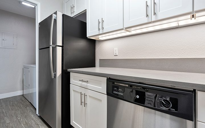 Unfurnished kitchen with white cabinets, range, and fridge at Willow Creek, San Jose apartments