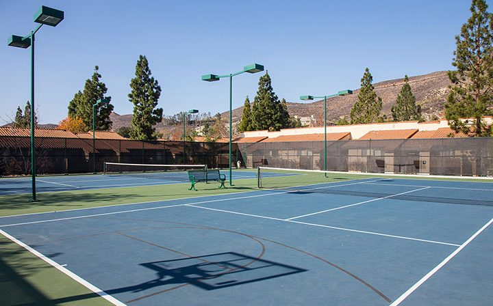 Blue basketball court with tall lights on clear day at Wood Ranch, apartments in Simi Valley