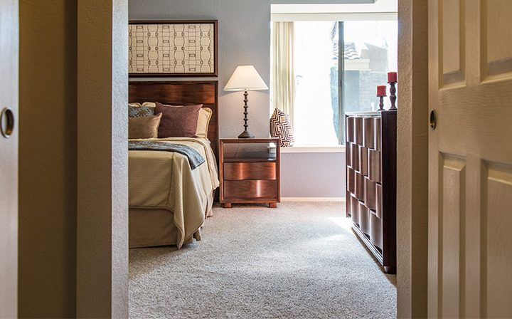 Hallway to carpeted, furnished bedroom with natural light at Wood Ranch, Simi Valley apartments