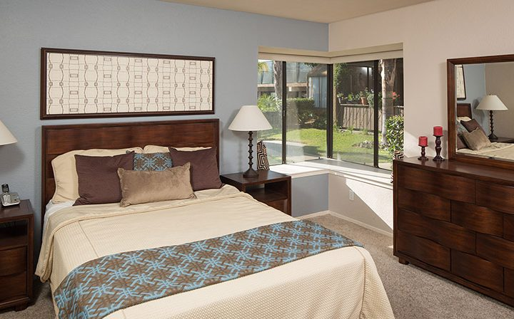Blue accent wall in furnished bedroom with corner windows at Wood Ranch, Simi Valley apartments