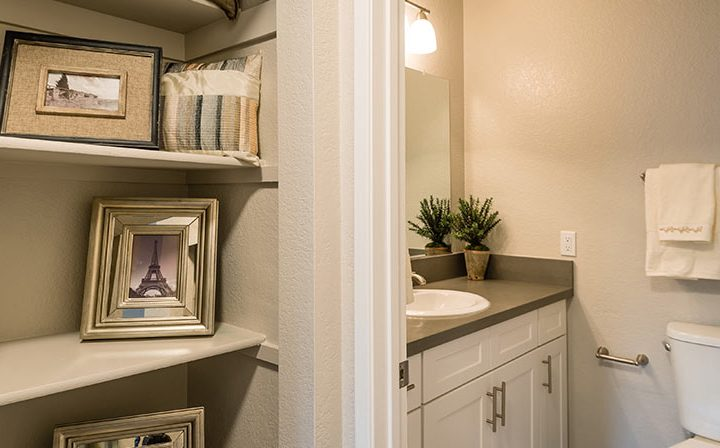 Closet with art on shelves next to furnished bathroom at Wood Ranch, Simi Valley apartments