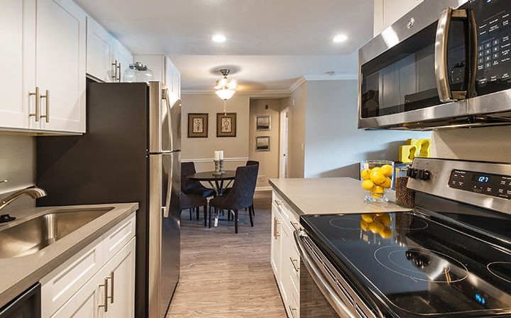 Kitchen with white cabinets and range opposite sink at Wood Ranch, Simi Valley apartments