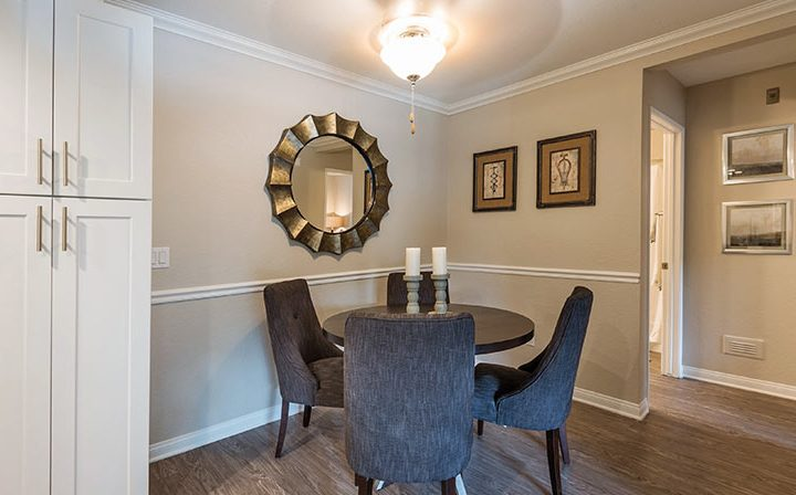 Furnished dining room with circular mirrors and table at Wood Ranch, Simi Valley apartments