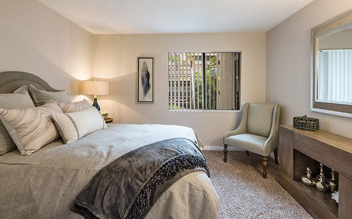 Furnished bedroom with carpeting and mirror at Wood Ranch, apartments in Simi Valley