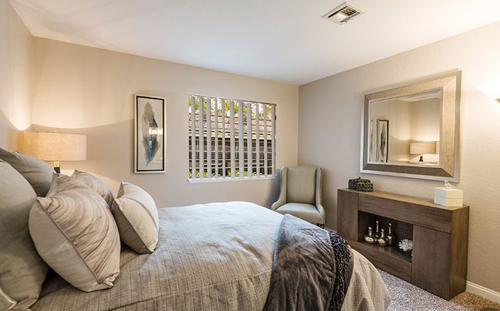 Carpeted bedroom furnished with bed, mirror, and art at Wood Ranch, Simi Valley apartments