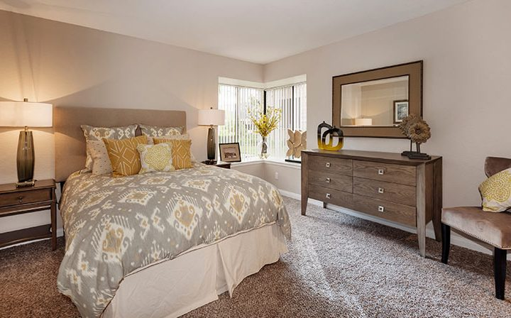 Furnished bedroom with corner windows and carpet at Wood Ranch, apartments in Simi Valley