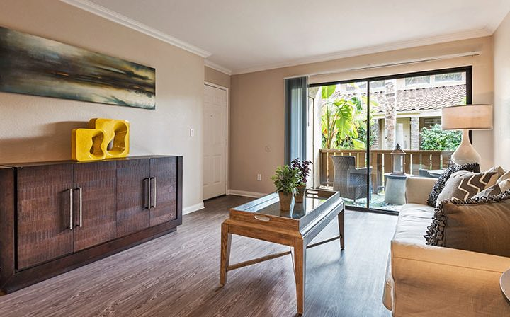 Sunny, large living room with art and patio exit at Wood Ranch, apartments in Simi Valley