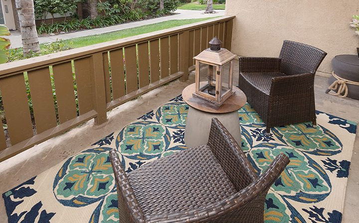 Balcony franchised with rug and wicker chairs at Wood Ranch, Simi Valley apartments