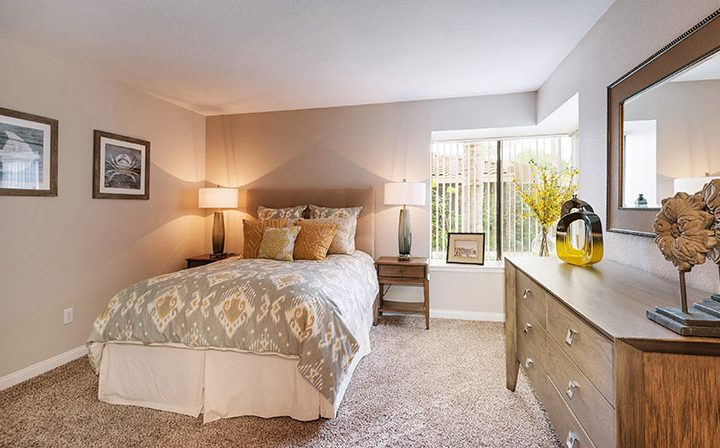 Carpeted, furnished bedroom with ample natural light at Wood Ranch, apartments in Simi Valley