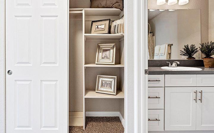 Open closet with art on shelves next to bathroom at Wood Ranch, apartments in Simi Valley
