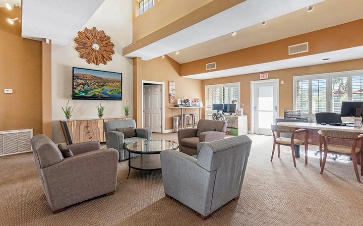 Clubhouse with comfortable seating and orange walls at Wood Ranch, apartments in Simi Valley