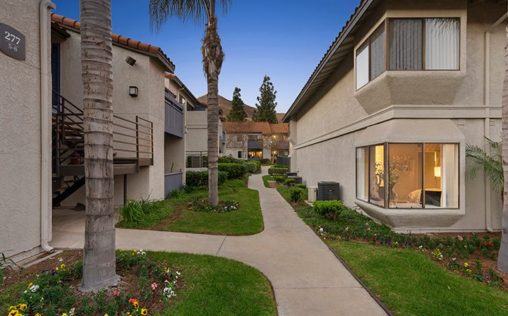 Paved path between apartments with grass and trees at Wood Ranch, Simi Valley apartments