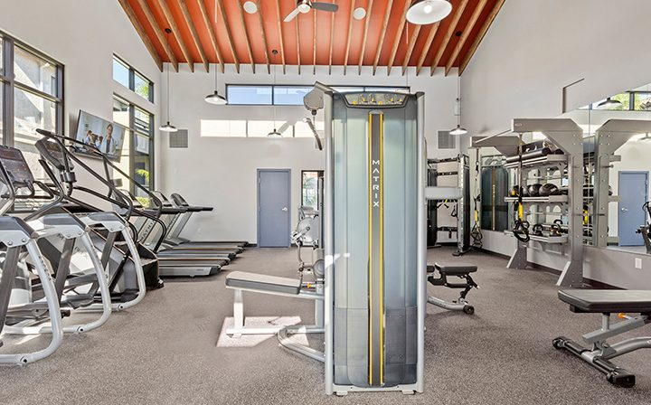 Large fitness center with machines and white walls at Wood Ranch, Simi Valley apartments