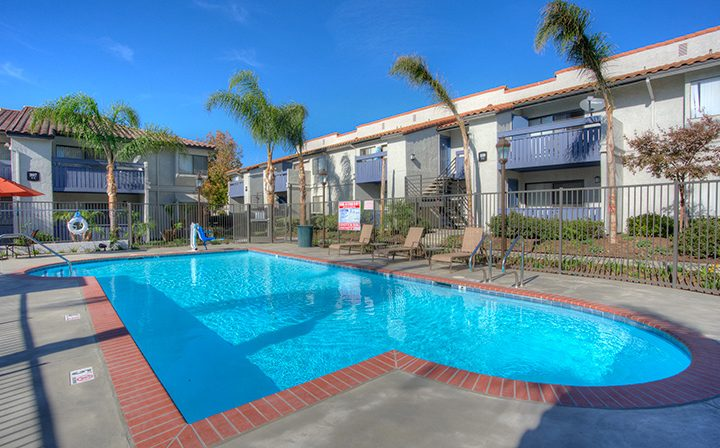 Large pool with seating on clear day next to units and trees at Wood Ranch, Simi Valley apartments