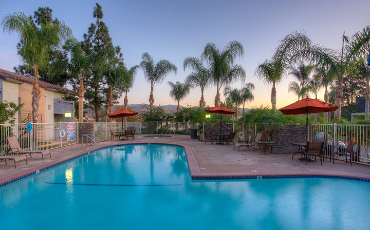 Resort-style pool at sunset in front trees at Wood Ranch, apartments in Simi Valley