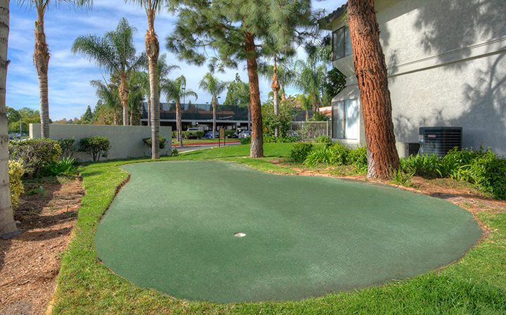 Putting green next to trees and grass at Wood Ranch, Simi Valley apartments